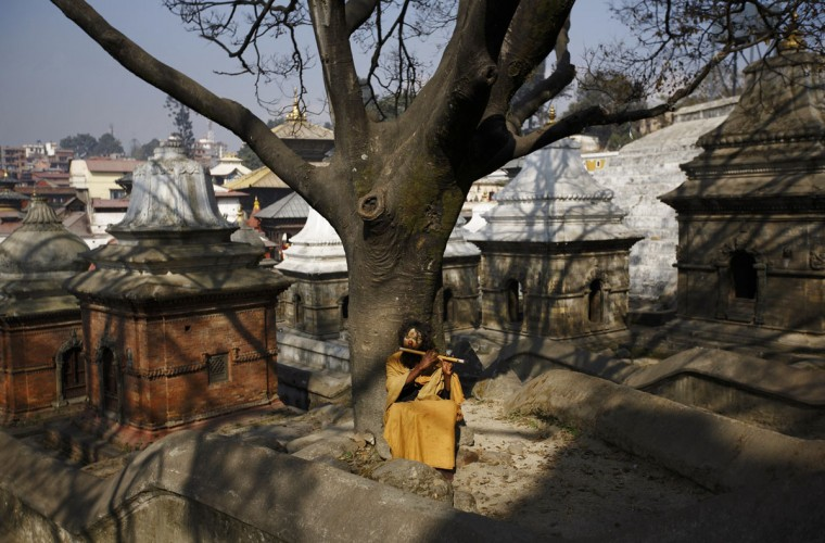 A Sadhu or Hindu holy man plays a flute as he sits under a tree at the premises of Pashupatinath Temple in Kathmandu December 12, 2013. (REUTERS/Navesh Chitrakar)