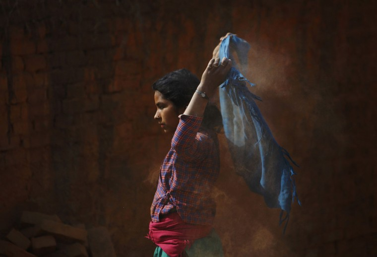 A girl removes dust from her scarf as she works to earn money by carrying bricks at a brick factory in Lalitpur December 20, 2013. (REUTERS/Navesh Chitrakar)