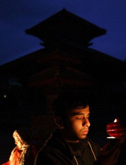 A man offers a butter lamp during evening prayers on the eve of New Year at Hanumandhoka Durbar Square in Kathmandu December 31, 2013. (REUTERS/Navesh Chitrakar)