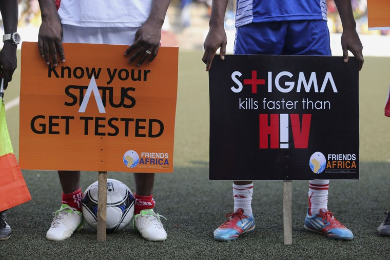 Banners for AIDS awareness are held by soccer players during a charity match for World AIDS Day in Lagos, Nigeria, November 30, 2013. World AIDS Day is observed annually on December 1. (Akintunde Akinleye/Reuters)