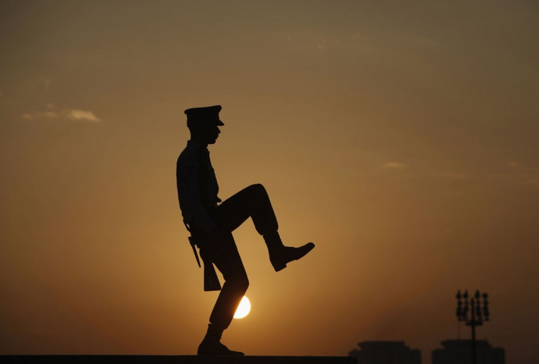 A cadet from the Pakistan Air Force (PAF) is silhouetted against the morning sun during the guard mounting ceremony at the mausoleum of Mohammad Ali Jinnah in Karachi, December 25, 2013. A contingent of Pakistan Military Academy (PMA) cadets mounted the guard at the mausoleum of Mohammad Ali Jinnah to mark his 137th birth anniversary. Jinnah is generally regarded as the founder of Pakistan. (Akhtar Soomro/Reuters)