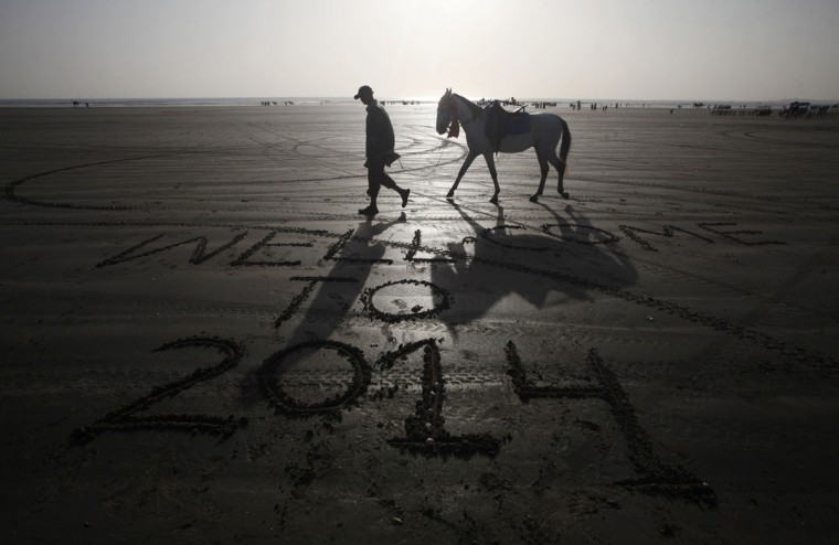 A man leads his horse as he walks past a message left by a visitor on New Year's Eve, along Karachi's Clifton Beach December 31, 2013. (REUTERS/Athar Hussain)