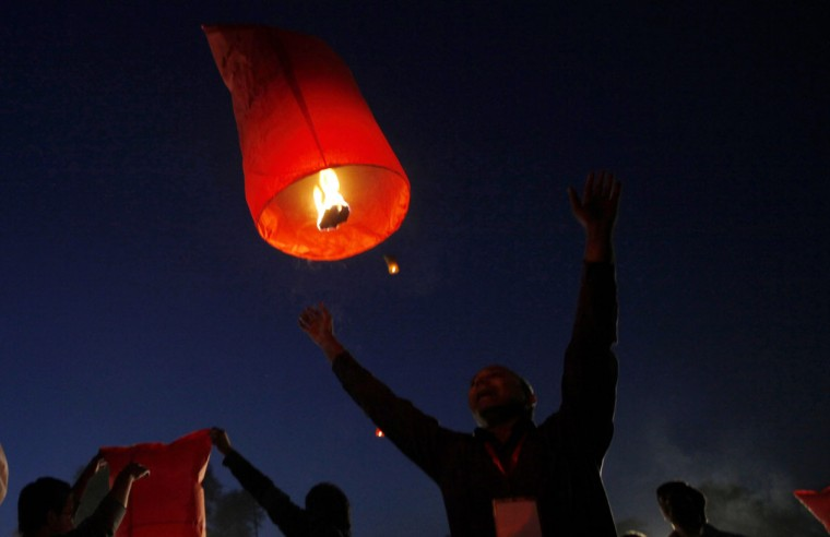 A man launches a sky lantern during a ceremony to raise awareness about AIDS on the eve of World AIDS Day in Lahore, Pakistan, November 30, 2013. (Mohsin Raza/Reuters)