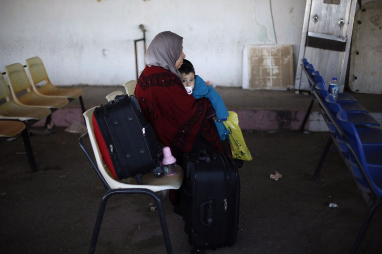 A Palestinian woman, hoping to cross into Egypt, holds a boy as they wait at the Rafah crossing between Egypt and the southern Gaza Strip December 24, 2013. Egyptian authorities partially opened the Rafah crossing, Gaza's main window to the world, on Tuesday for three days, border officials said. Since July, the authorities have kept the crossing largely closed, only opening it partially for humanitarian purposes. (REUTERS/Ibraheem Abu Mustafa)