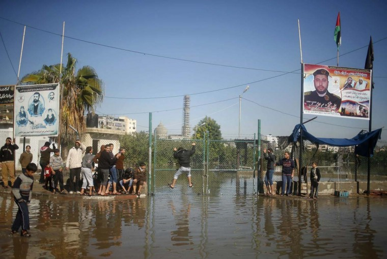 "A Palestinian youth climbs a gate to cross a road flooded with rainwater in the northern Gaza Strip December 15, 2013. More than 5,000 people have been evacuated from flood-damaged homes in northern Gaza and at least one person killed in what the United Nations called ""a disaster area"". Mohammed Salem/Reuters)"