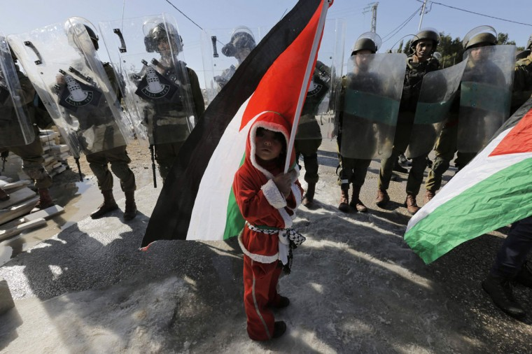 A Palestinian boy dressed as Santa Claus holds a Palestinian flag as he stands in front of Israeli soldiers during a protest against the controversial Israeli barrier in the West Bank village of al-Masara near Bethlehem December 20, 2013. (REUTERS/Ammar Awad)