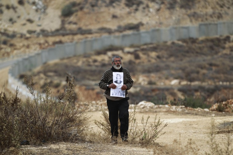 The controversial Israeli barrier is seen in the background as a Palestinian protester walks with placards depicting former South African President Nelson Mandela during a weekly demonstration against Jewish settlements in the West Bank village of Bilin, near Ramallah December 6, 2013. South African anti-apartheid hero Mandela died peacefully at home at the age of 95 on Thursday after months fighting a lung infection, leaving his nation and the world in mourning for a man revered as a moral giant. (REUTERS/Mohamad Torokman)