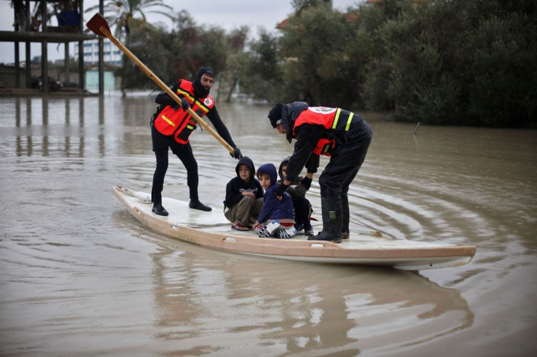Members of the Palestinian civil defense ride a boat as they evacuate boys following heavy rains on a stormy day in Rafah, in the southern Gaza Strip, December 12, 2013. (REUTERS/Ibraheem Abu Mustafa)