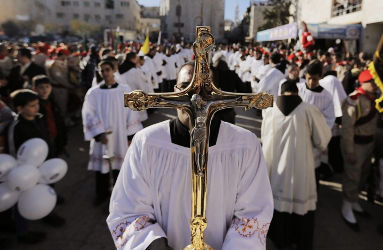 A priest holds a cross as he awaits the arrival of the Latin Patriarch of Jerusalem Fouad Twal, outside the Church of Nativity, the site revered as the birthplace of Jesus, during Christmas celebrations in the West Bank town of Bethlehem December 24, 2013. (REUTERS/Ammar Awad)