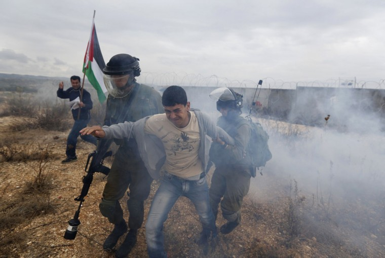 Israeli soldiers detain a Palestinian protester during clashes at a weekly demonstration against Jewish settlements in the West Bank village of Bilin, near Ramallah December 6, 2013. (REUTERS/Mohamad Torokman)