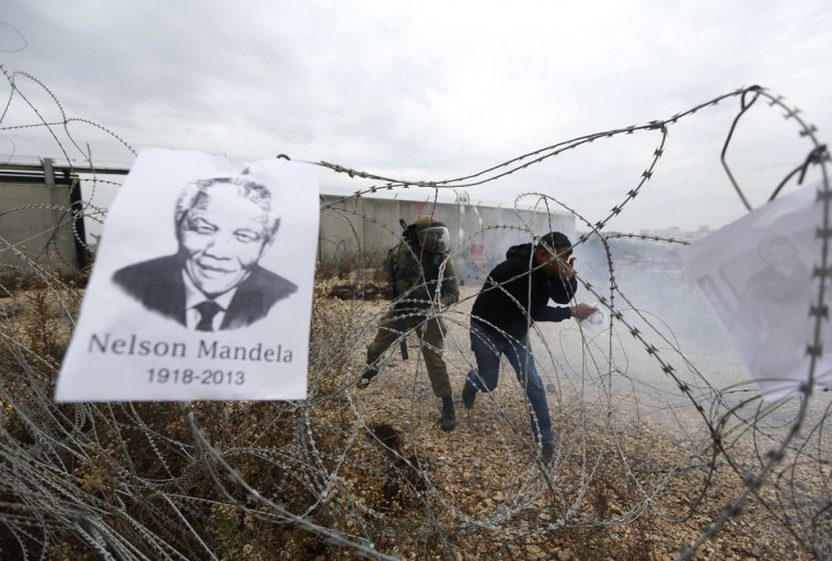 A placard depicting former South African President Nelson Mandela hangs on a barbed wire as a Palestinian protester reacts to tear gas fired by Israeli soldiers during clashes at a weekly demonstration against Jewish settlements in the West Bank village of Bilin, near Ramallah December 6, 2013. South African anti-apartheid hero Mandela died peacefully at home at the age of 95 on Thursday after months fighting a lung infection, leaving his nation and the world in mourning for a man revered as a moral giant. (REUTERS/Mohamad Torokman)
