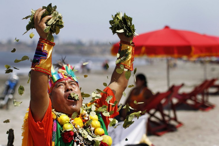 A Shaman holds bunches of coca leaves, a cash crop native to western South America, while performing a ceremony of predicting the upcoming year at Agua Dulce Beach in Lima December 30, 2013. (REUTERS/Enrique Castro-Mendivil)