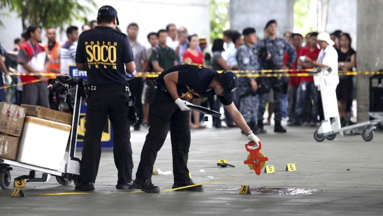 Police investigators work at the crime scene after a local town mayor was ambushed in a shooting attack at Manila's Ninoy Aquino International Airport December 20, 2013. Gunmen on Friday shot dead the town mayor and three other people at the airport in the Philippine capital, Manila, sending travellers fleeing for safety, authorities said. Ukol Talumpa was mayor of a town called Labangan, Zamboanga del Sur. Three passengers were also killed and four people were wounded, airport manager Jose Honrado said. (REUTERS/Che Cillo)