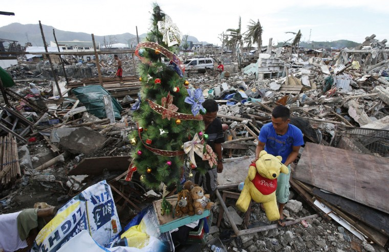 A typhoon survivor decorates a Christmas tree amidst the rubble of destroyed houses in Tacloban city in central Philippines December 17, 2013. Super typhoon Haiyan reduced almost everything in its path to rubble when it swept ashore in the central Philippines on November 8, killing at least 6,069 people, leaving 1,779 missing and 4 million either homeless or with damaged homes. (Erik De Castro/Reuters)
