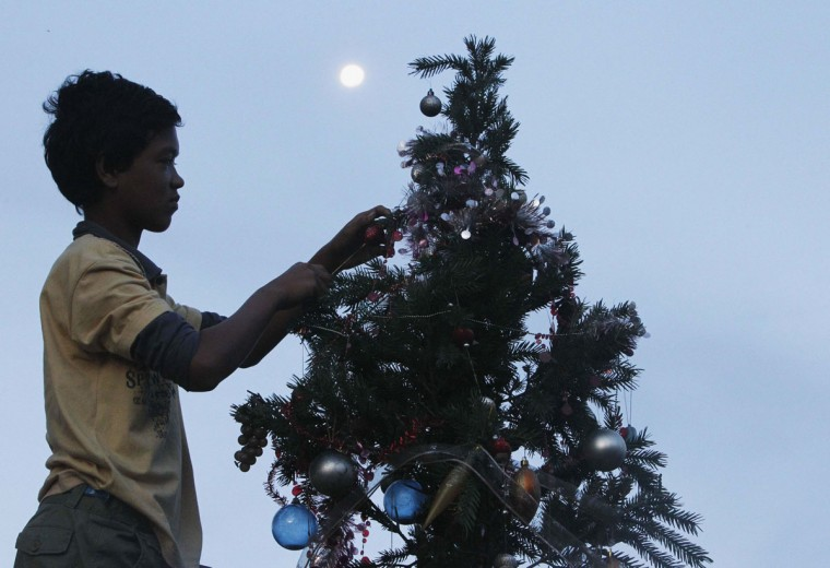 Ruben Miraflor, 15, a survivor of Super Typhoon Haiyan, decorates a Christmas tree placed along a main street at Magallanes town in Tacloban city, central Philippines December 20, 2013. Super typhoon Haiyan reduced almost everything in its path to rubble when it swept ashore in the central Philippines on November 8, killing at least 6,069 people, leaving 1,779 missing and 4 million either homeless or with damaged homes. (REUTERS/Romeo Ranoco)