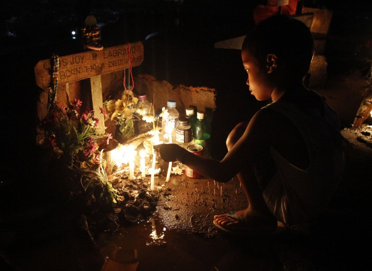 Darren Fabella, 6, lights candles for his departed friend, a victim of the onslaught of super typhoon Haiyan a month ago, who was buried in a vacant lot on Christmas Eve in front of a Catholic church in San Joaquin town in Palo, Leyte province central Philippines December 24, 2013. Super typhoon Haiyan reduced almost everything in its path to rubble when it swept ashore in the central Philippines on November 8, killing at least 6,069 people, leaving 1,779 missing and 4 million either homeless or with damaged homes. (REUTERS/Romeo Ranoco)