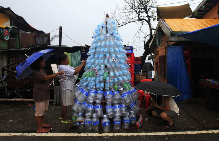 Victims of super Typhoon Haiyan decorate their improvised Christmas tree with empty cans and bottles at the ravaged town of Anibong, Tacloban city, central Philippines December 24, 2013, a month after Typhoon Haiyan battered central Philippines. Super typhoon Haiyan reduced almost everything in its path to rubble when it swept ashore in the central Philippines on November 8, killing at least 6,069 people, leaving 1,779 missing and 4 million either homeless or with damaged homes. (REUTERS/Romeo Ranoco)