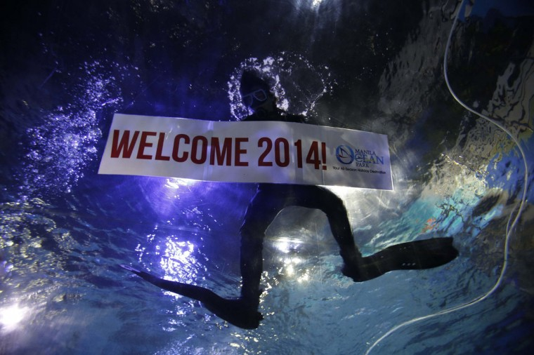 "A professional diver holds a ""Welcome 2014"" banner while swimming during New Year celebrations inside a large aquarium at a ocean park in Manila December 31, 2013. Neither an earthquake nor a super typhoon have dampened the country's optimism as 94 percent are entering the New Year with hope instead of fear, according to a new survey by pollster Social Weather Stations reported on Tuesday. (REUTERS/Romeo Ranoco)"