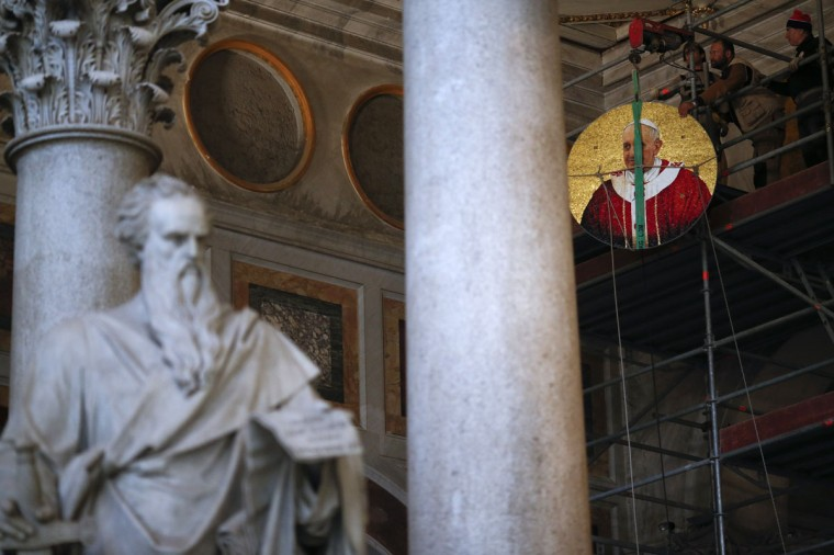 Workers lift up a mosaic depicting Pope Francis before installing it at Saint Paul's Basilica in Rome December 9, 2013. (Alessandro Bianchi/REUTERS)