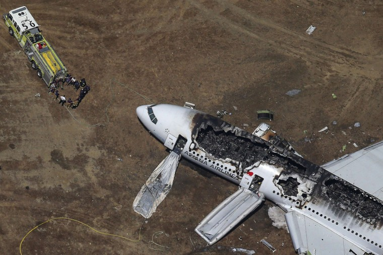 Rescue officials stand near an Asiana Airlines Boeing 777 plane after it crashed while landing at San Francisco International Airport in California July 6, 2013. Two people were killed and 130 were hospitalized after the plane crash-landed, San Francisco Fire Department Chief Joanna Hayes-White said. The figures cited by Hayes-White left 69 people still unaccounted for in the accident. The Boeing 777, which had flown from Seoul, South Korea, was carrying 307 people. (Jed Jacobsohn/Reuters)