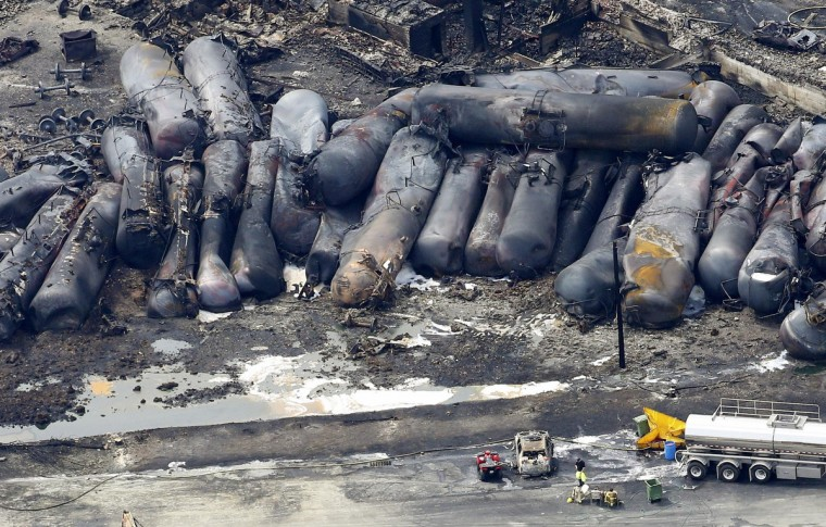 A firefighter stands near the wreckage of a train derailment and explosion, in Lac-Megantic July 8, 2013. The driverless, runaway fuel train that exploded in a deadly ball of flames in the centre of the small Quebec town started rumbling down an empty track just minutes after a fire crew had extinguished a blaze in one of its parked locomotives, an eyewitness said. (Mathieu Belanger/Reuters)
