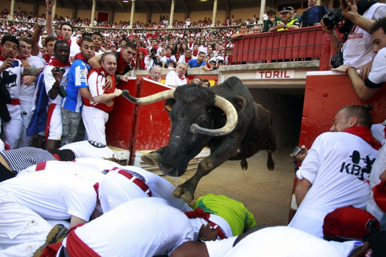 A fighting cow leaps over revelers into the bull ring after the fourth running of the bulls at the San Fermin festival in Pamplona July 10, 2013. (Joseba Etxaburu/Reuters)