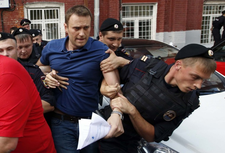 "Policemen detain Russian opposition leader and anti-corruption blogger Alexei Navalny (C), after he visited the city's election commission office to submit documents to be registered as a mayoral election candidate, in Moscow July 10, 2013. Protest leader Navalny said on July 5 he would destroy the political system under Russian President Vladimir Putin that was ""sucking the blood out of Russia"", after state prosecutors demanded he be jailed for six years on theft charges. Other opposition figures say the trial is intended to prevent Navalny from fulfilling his dream of becoming president, and before that, running for Moscow mayor in September. Navalny was detained on the charge of organising an unsanctioned rally near the city's election commission office and was then released in less than half an hour. (Grigory Dukor/Reuters)"