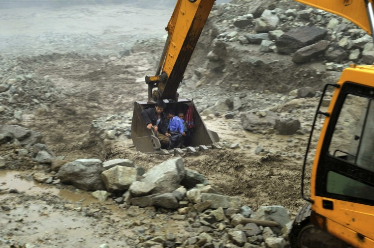 An excavator is used to move villagers away from a flooded area during heavy rainfall in Yingxiu, Wenchuan county, Sichuan province, July 10, 2013. More than 300 hundred people were evacuated in Yingxiu after roads connecting the township to the outside world were cut off by floods and landslides. (Reuters)