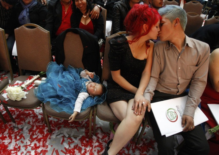 A newlywed couple kisses as their baby sleeps during a mass wedding on Valentine's Day in Ciudad Juarez February 14, 2013. About 3,400 couples tied the knot in the mass wedding ceremony organized by the Civil Registry and the state government to formalise their relationships by entering an alternative legal status and to commemorate Valentine's Day, local media reported. (Jose Luis Gonzalez/Reuters)