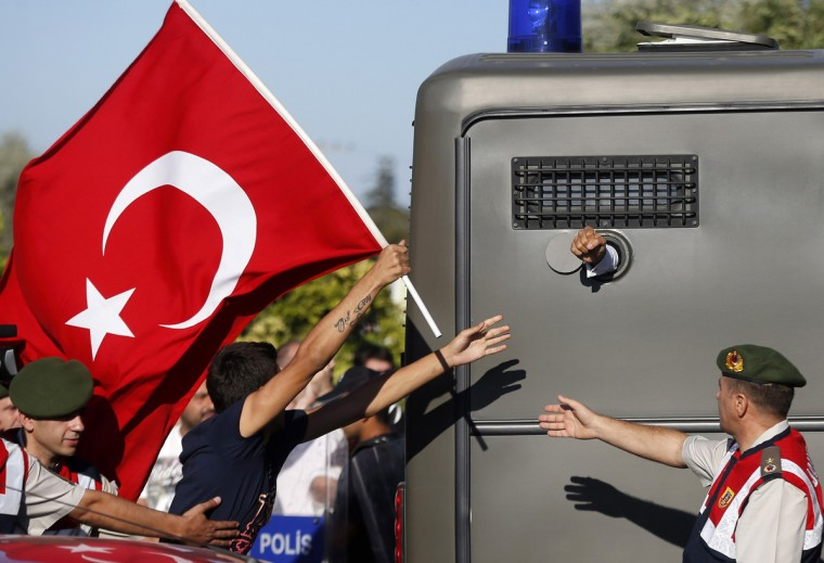 Protesters run after a prison van as an unidentified defendant sticks his fist out as he is driven to a courthouse in Silivri, where a hearing for people charged with attempting to overthrow Turkish Prime Minister Tayyip Erdogan's Islamist-rooted government is due to take place, August 5, 2013. A Turkish court began sentencing nearly 300 defendants accused of plotting to overthrow the government, handing prison sentences of up to 20 years to some and acquitting 21 others. The court was announcing the verdicts individually. (Murad Sezer/Reuters)