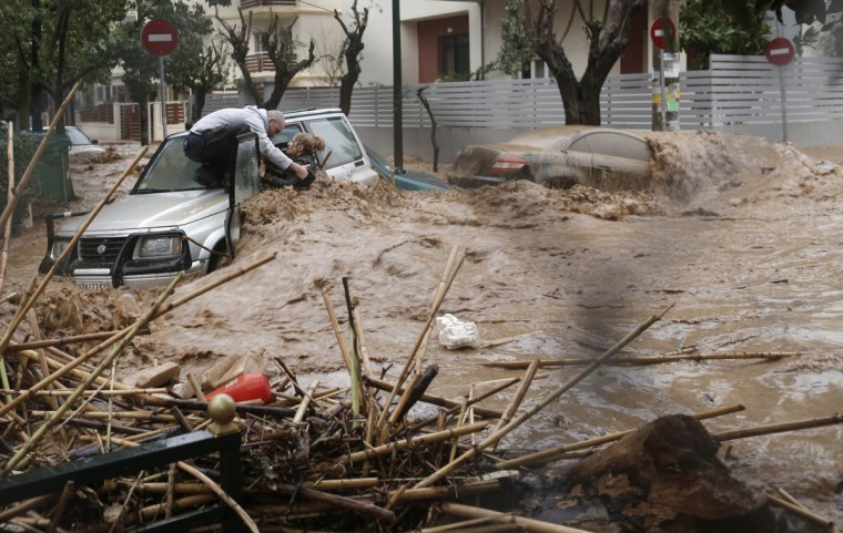 A woman is rescued from floodwaters by a resident standing on top of her car during heavy rain in the Chalandri suburb, north of Athens February 22, 2013. (John Kolesidis/Reuters)