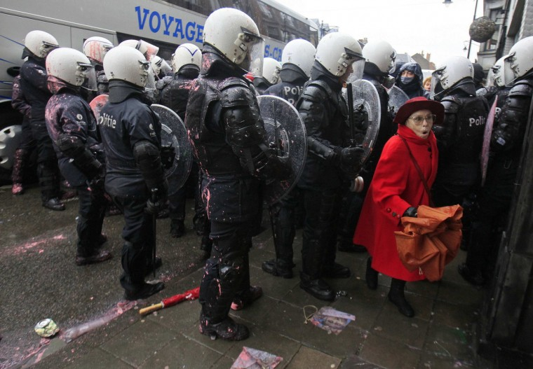 A woman walks behind Belgian riot policemen during clashes with Arcelor Mittal workers from several Liege steel plants demonstrating outside the Walloon Region parliament in Namur January 29, 2013. Arcelor Mittal, the world's largest steel producer, plans to shut a coke plant and six finishing lines at its site in Liege, Belgium, which will affect 1,300 employees, the group said. (Yves Herman/Reuters)