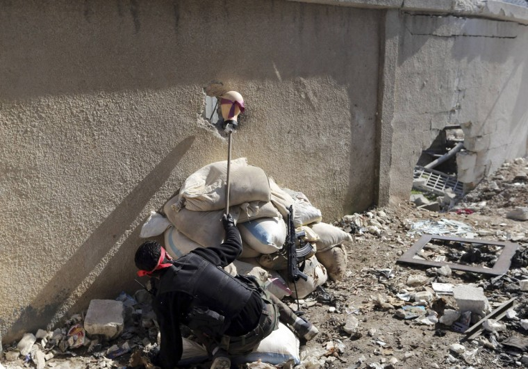 A Free Syrian Army fighter holds the head of a mannequin up to a hole in a wall of a Syrian Army base to attract and locate a sniper during heavy fighting in the Arabeen neighborhood of Damascus February 3, 2013. (Goran Tomasevic/Reuters)