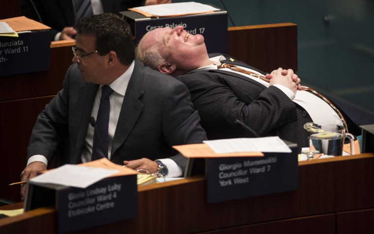 Toronto Mayor Rob Ford laughs during council beside councillor Giorgio Mammoliti at City Hall in Toronto November 14, 2013. Embattled mayor Ford, under huge pressure to quit after he admitted smoking crack cocaine, said then that he was getting help for a drinking problem, but offered no indication that he might step down. Ford also expressed remorse for an obscene outburst he made earlier in the day when denying an allegation he had made sexual overtures to a female member of his staff. (Mark Blinch/Reuters)