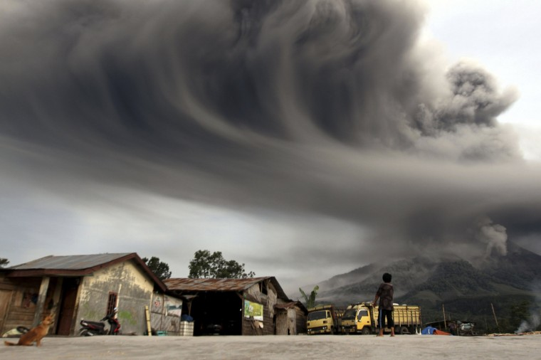 A woman looks on as Mount Sinabung spews ash, as pictured from Sibintun village in Karo district, Indonesia's north Sumatra province November 18, 2013. Mount Sinabung continued to spew volcanic ash throwing a plume 8,000 meters into the atmosphere as thousands of residents remained in temporary shelters fearful of more eruptions, according to local media. (Roni Bintang/Reuters)