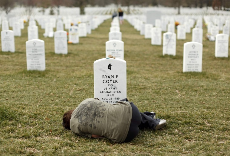 Lesleigh Coyer, 25, of Saginaw, Michigan, lies down in front of the grave of her brother, Ryan Coyer, who served with the U.S. Army in both Iraq and Afghanistan, at Arlington National Cemetery in Virginia March 11, 2013. Coyer died of complications from an injury sustained in Afghanistan. (Kevin Lamarque/Reuters)