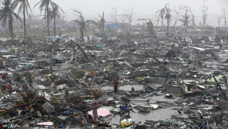 Survivors stand among debris and ruins of houses destroyed after Super Typhoon Haiyan battered Tacloban city in central Philippines November 10, 2013. Haiyan, one of the most powerful storms ever recorded killed at least 10,000 people in the central Philippines province of Leyte, a senior police official said, with coastal towns and the regional capital devastated by huge waves. Super typhoon Haiyan destroyed about 70 to 80 percent of the area in its path as it tore through the province on Friday, said chief superintendent Elmer Soria, a regional police director. (Erik De Castro/Reuters)