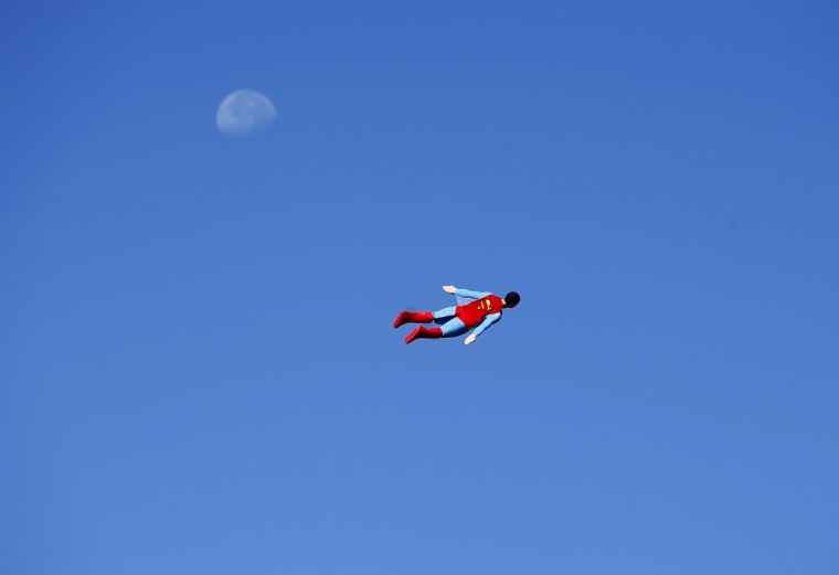 A radio-controlled Superman plane, flown by designer Otto Dieffenbach, passes the moon during a test flight in San Diego, California June 27, 2013. Otto and business partner Ed Hanley are a small start-up company that creates flying radio-controlled planes, designed in the form of people, characters and objects, for commercial and promotional uses. (Mike Blake/Reuters)