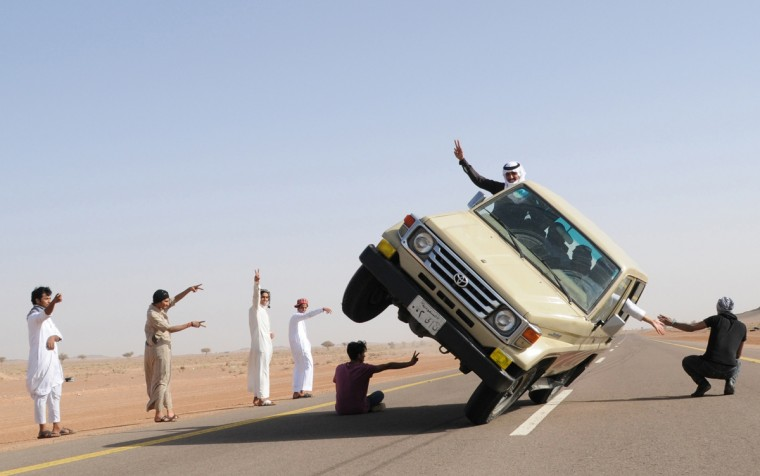 """Saudi youths demonstrate a stunt known as """"sidewall skiing"""" (driving on two wheels) in the northern city of Hail, in Saudi Arabia March 30, 2013. Performing stunts such as sidewall skiing and drifts is a popular hobby amongst Saudi youths. (Mohamed Al Hwaity/Reuters)"""