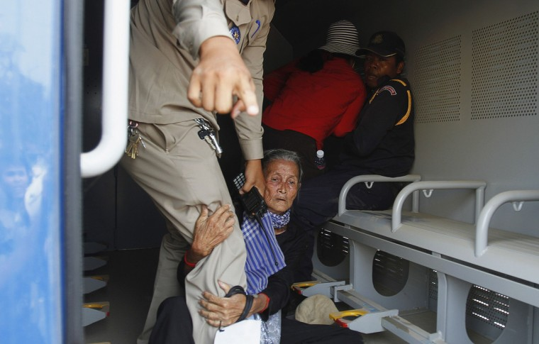 An elderly woman grabs the leg of a police officer as residents of Boeung Kak Lake community are arrested in a police truck during a protest in Phnom Penh March 13, 2013. The residents of Boeung Kak Lake have been embroiled in a long-running land dispute with a real estate development firm in the capital, and are also appealing for the release of another resident, Yorm Bopha, from prison. (Samrang Pring/Reuters)