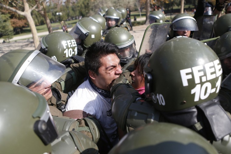 A student protester bites a riot policeman while being detained during a riot at a rally demanding Chile's government reform the education system in Santiago, May 8, 2013. (Ivan Alvarado/Reuters)