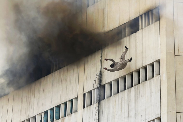 A man falls from a high floor of a burning building in central Lahore May 9, 2013. Fire erupted on the seventh floor of the LDA plaza in Lahore and quickly spread to higher floors leaving many people trapped inside the building. At least three people fell from the high floors trying to avoid the fire that engulfed the building, local media reports. (Damir Sagolj/Reuters)
