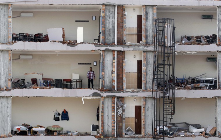 """A man checks an apartment on a damaged building at the site of a blast in the town of Reyhanli in Hatay province, near the Turkish-Syrian border, May 13, 2013. Syria's information minister has blamed Turkey's government for deadly car bombings near the Syrian border and branded Prime Minister Tayyip Erdogan a """"murderer"""", state-run Russian TV company RT reported. It said he repeated a denial of Syrian involvement in car bombings that killed 46 people on Saturday in the Turkish border town of Reyhanli. Turkey has accused a group with links to Syrian intelligence of carrying out the attacks. (Umit Bektas/Reuters)"""