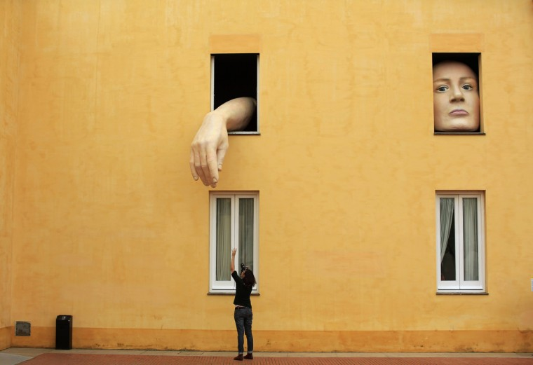 """A woman takes pictures of art installation """"Alice"""" by Spanish artist Cristina Lucas in the Andalusian Centre of Contemporary Art in the Andalusian capital of Seville, southern Spain April 10, 2013. (Marcelo del Pozo/Reuters)"""