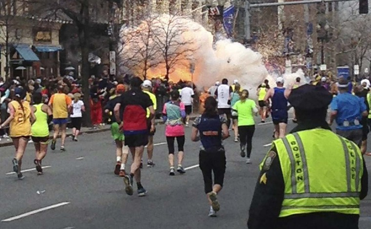 Runners continue to run towards the finish line of the Boston Marathon as an explosion erupts near the finish line of the race in this photo exclusively licensed to Reuters by photographer Dan Lampariello after he took the photo in Boston, Massachusetts, April 15, 2013. Two simultaneous explosions ripped through the crowd at the finish line of the Boston Marathon, killing at least two people and injuring dozens on a day when tens of thousands of people pack the streets to watch the world famous race. (Dan Lampariello/Reuters)