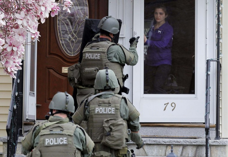 A member of the SWAT team motions to a resident to come out of the house as they conduct a house to house search for Dzhokar Tsarnaev, the one remaining suspect in the Boston Marathon bombing, in Watertown, Massachusetts April 19, 2013. Police killed one suspect in the Boston Marathon bombing, Tamerlan Tsarneav, in a shootout and mounted house-to-house searches for the second man, his brother Dzhokar Tsarnaev, in the Boston suburb of Watertown, officials said then, with much of the city under virtual lockdown after a bloody night of shooting and explosions in the streets. (Jessica Rinaldi/Reuters)