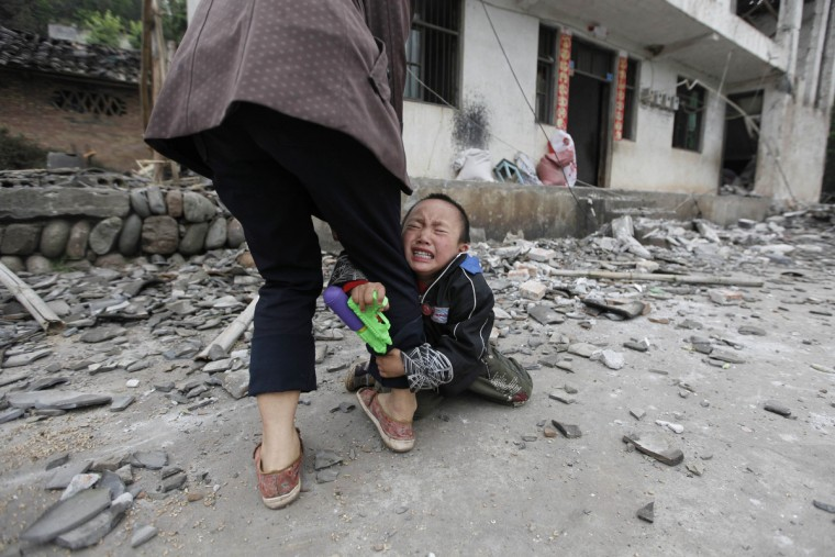 A boy holds his mother's leg as he cries in front of their damaged house after a strong 6.6 magnitude earthquake at Longmen village, Lushan county in Ya'an, Sichuan province April 21, 2013. Rescuers poured into a remote corner of southwestern China on Sunday as the death toll from the country's worst earthquake in three years climbed to 164 with more than 6,700 injured, state media said. (Jason Lee/Reuters)