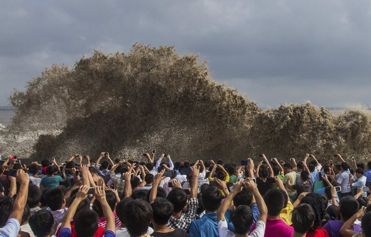 Visitors take pictures of tidal waves under the influence of Typhoon Usagi in Hangzhou, Zhejiang province, September 22, 2013. According to official Xinhua news agency, China's National Meteorological Center issued its highest alert, warning that Usagi would bring gales and downpours to southern coastal areas. (Chance Chan/Reuters)