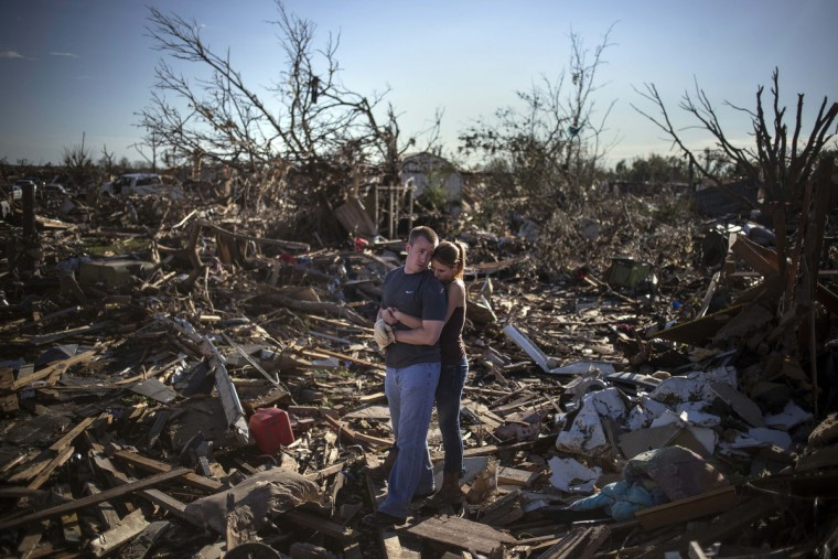 Danielle Stephan holds boyfriend Thomas Layton as they pause between salvaging through the remains of a family member's home one day after a tornado devastated the town Moore, Oklahoma, in the outskirts of Oklahoma City May 21, 2013. Rescuers went building to building in search of victims and thousands of survivors were homeless after a massive tornado tore through the Oklahoma City suburb of Moore, wiping out whole blocks of homes and killing at least 24 people. (Adrees Latif/Reuters)