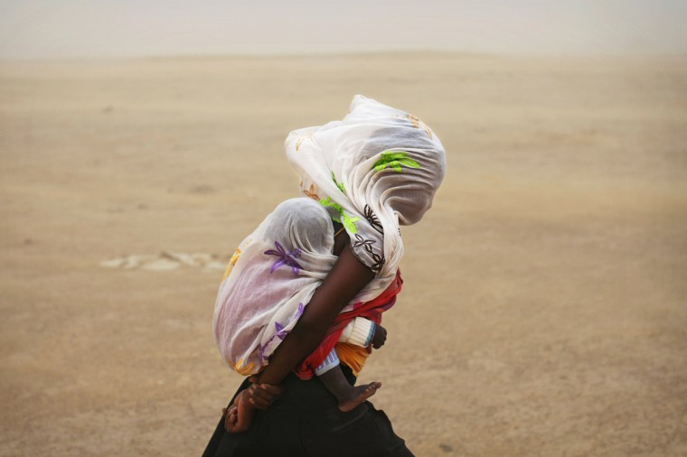 A woman carrying her baby and wrapped with a shawl walks through a sandstorm in Timbuktu July 29, 2013. (Joe Penney/Reuters)